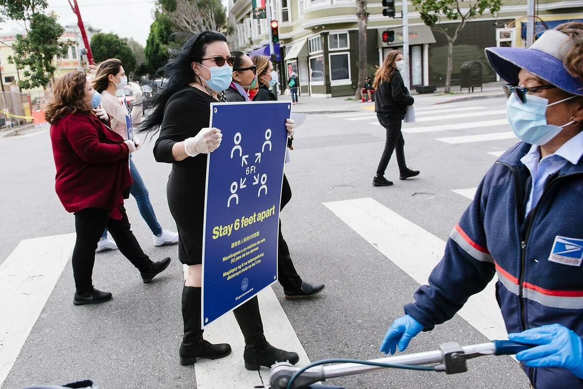 San Francisco Latino Task Force on COVID-19 member Valerie Tulier-Laiwa, holds a social distancing poster as her group crosses 24th Street while putting up signs, in San Francisco, Calif, on Friday, April 17, 2020.