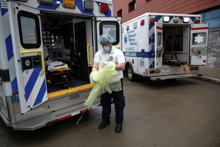 A medic removes his personal protective equipment after transporting a patient with possible COVID-19 symptoms to Stamford Hospital on April 03, 2020 in Stamford, Connecticut. Photo: John Moore / Getty Images / 2020 Getty Images