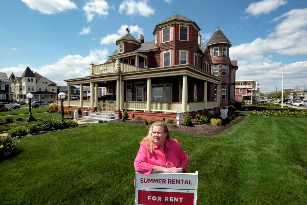 Real estate agent Michele DeRose stands outside a summer rental across from the beach in Ocean Grove, N.J. The six-bedroom, five-bath home still has weekly bookings available.