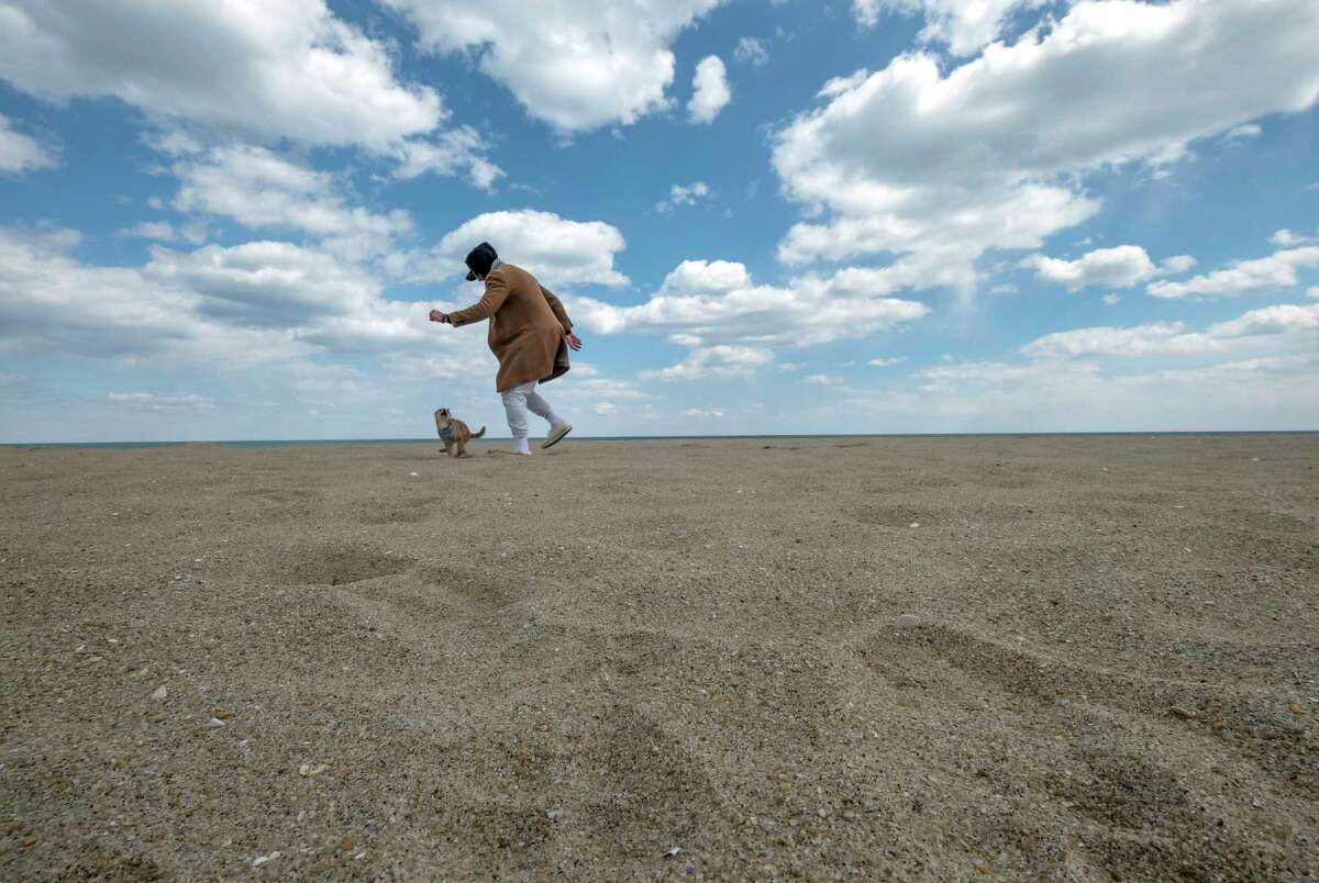 Taylor Negron plays with his puppy, Kairi, on the beach in Asbury Park, N.J.