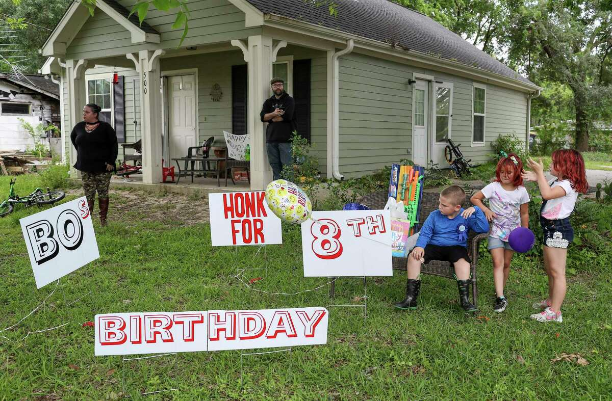 Bo Singleterry, front right, celebrates his eighth birthday with his cousins Brooke Crawford, 6, front center, and LeAnna Crawford, 7, front left, Friday, April 17, 2020, at his home in Anahuac. His parents had to cancel the birthday party sleep-over they had planned, but they arranged for a car parade to go by their house and honk for him.