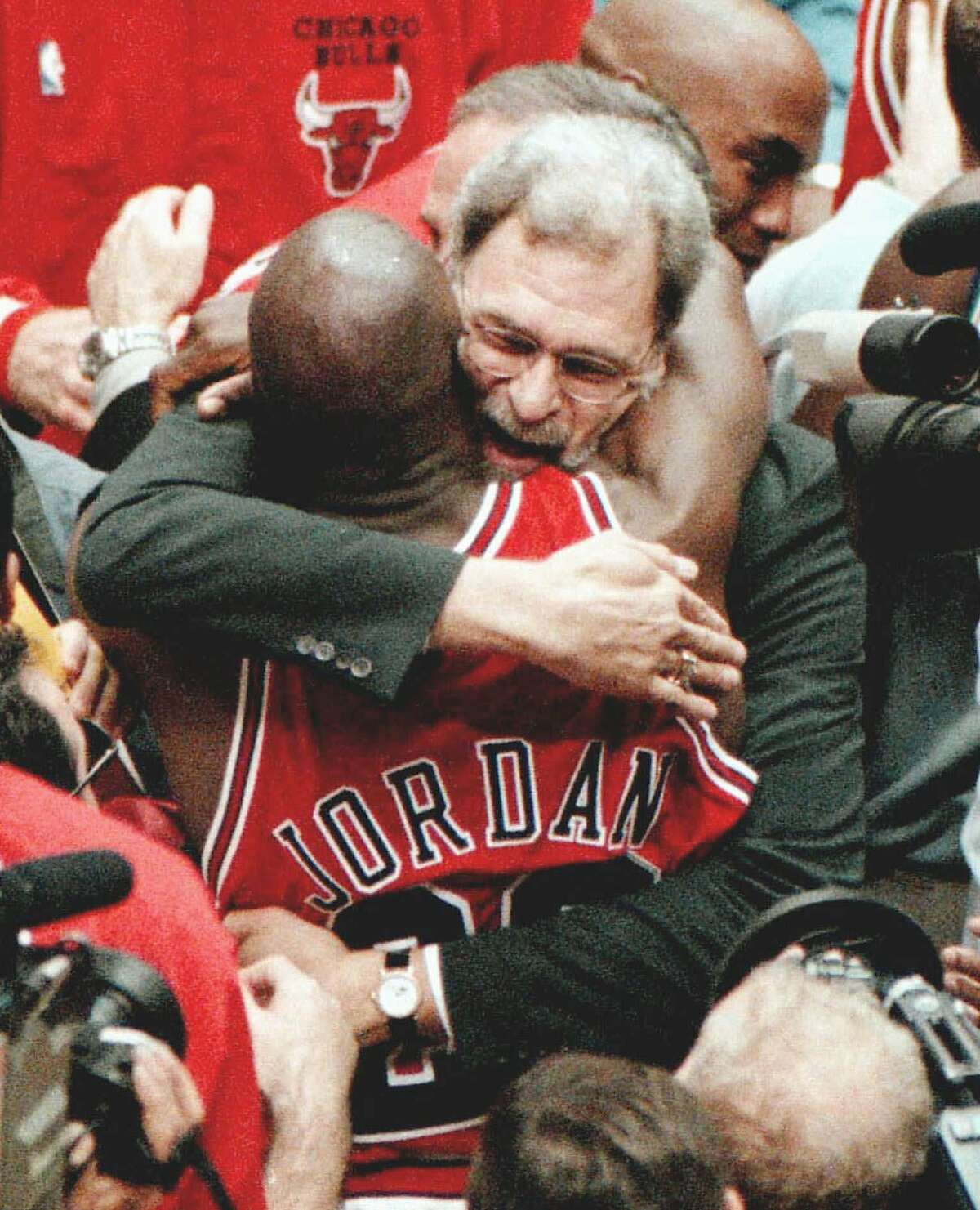 Chicago Bulls coach Phil Jackson and Michael Jordan embrace after the Bulls won their 6th NBA championship with an 87-86 win over the Utah Jazz in Game 6 on Sunday, June 14, 1998, at the Delta Center in Salt Lake City. (AP Photo/Chicago Tribune, Nuccio DiNuzzio) HOUCHRON CAPTION (06/16/1998): Michael Jordan would love to see Phil Jackson return, but don't count on it.