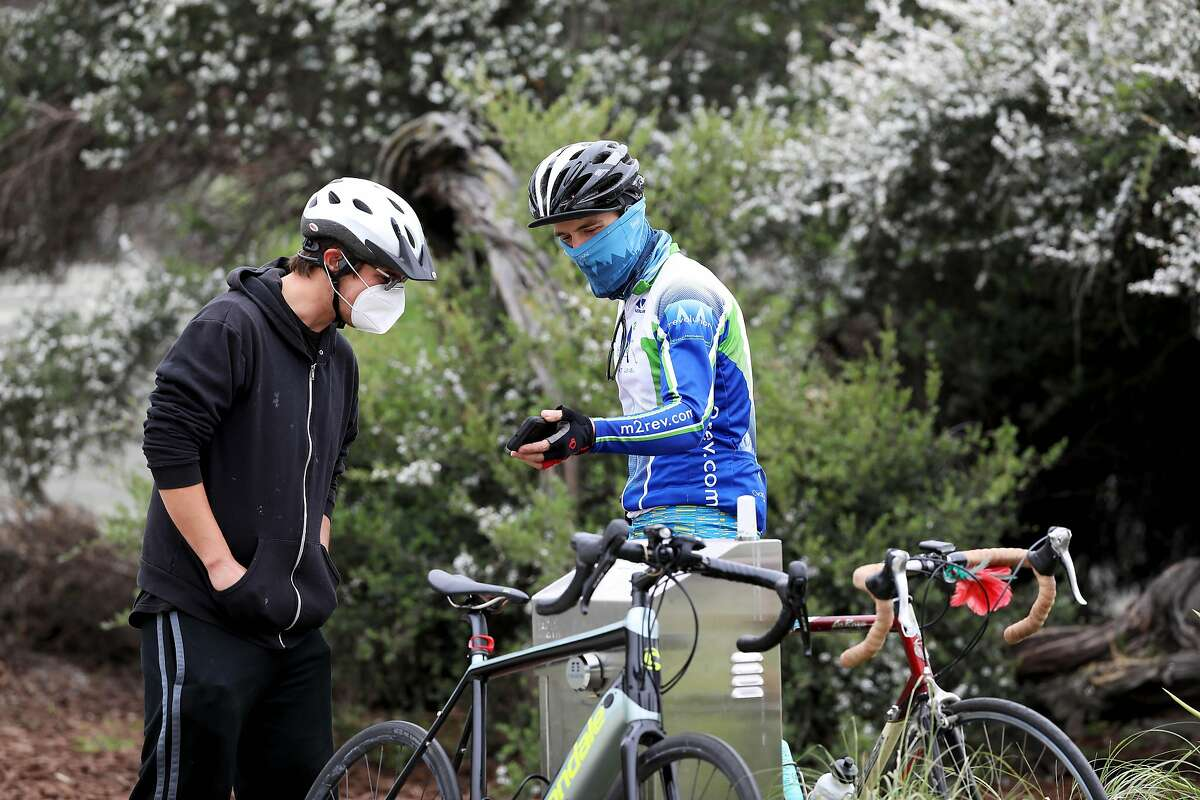 Andrew Sparks, left, dons a mask as he looks at a phone while standing near a man, who didn't want to provide his name, as they converse at Lake Merritt on Friday, April 17, 2020, in Oakland, Calif. Bay Area counties are expected to announce a new order requiring residents to wear masks/facial coverings beginning at noon next Wednesday. The move accompanies an expected move to relax elements of the stay at home orders starting in early May.