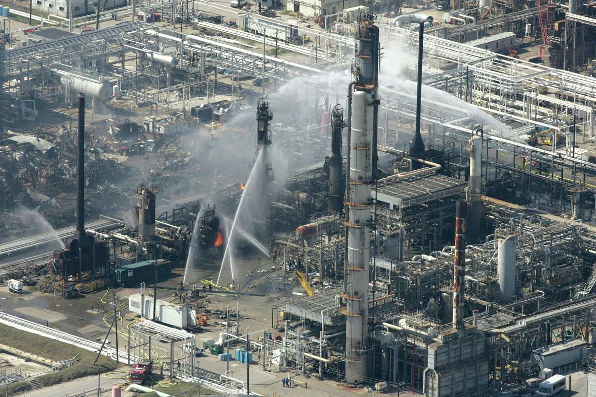 Firefighters pour water on a smoldering unit following an explosion that killed 15 people and injured more than 170 at the BP refinery in this March 23, 2005, file photo in Texas City, Texas. Internal documents show that budget cuts and a lack of leadership contributed to significant safety problems at BP PLC's Texas City plant, the site of last year's deadly explosion, federal investigators said Monday, Oct. 30, 2006. (AP Photo/Houston Chronicle, Brett Coomer, file)