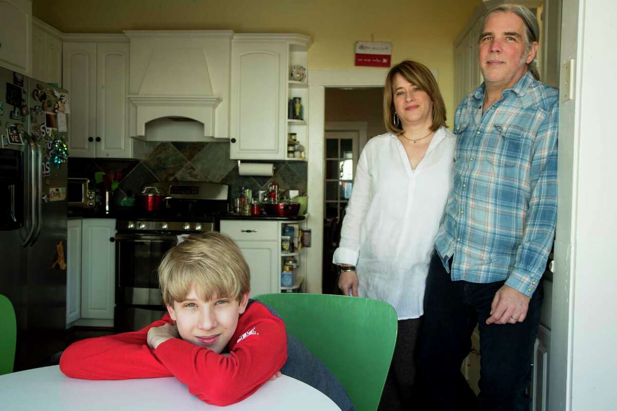 Isaac Heider, 12, sits in the kitchen table with his parents, Carol and Clinton, as they continue to ride out the shelter in place measures due to the coronavirus on Tuesday, April 14, 2020 in Houston. COVID-19 is the latest in a string of major events that have affected young children during the past few years, following Harvey and Imelda. The Heiders were flooded out of their Meyerland home during Harvey.