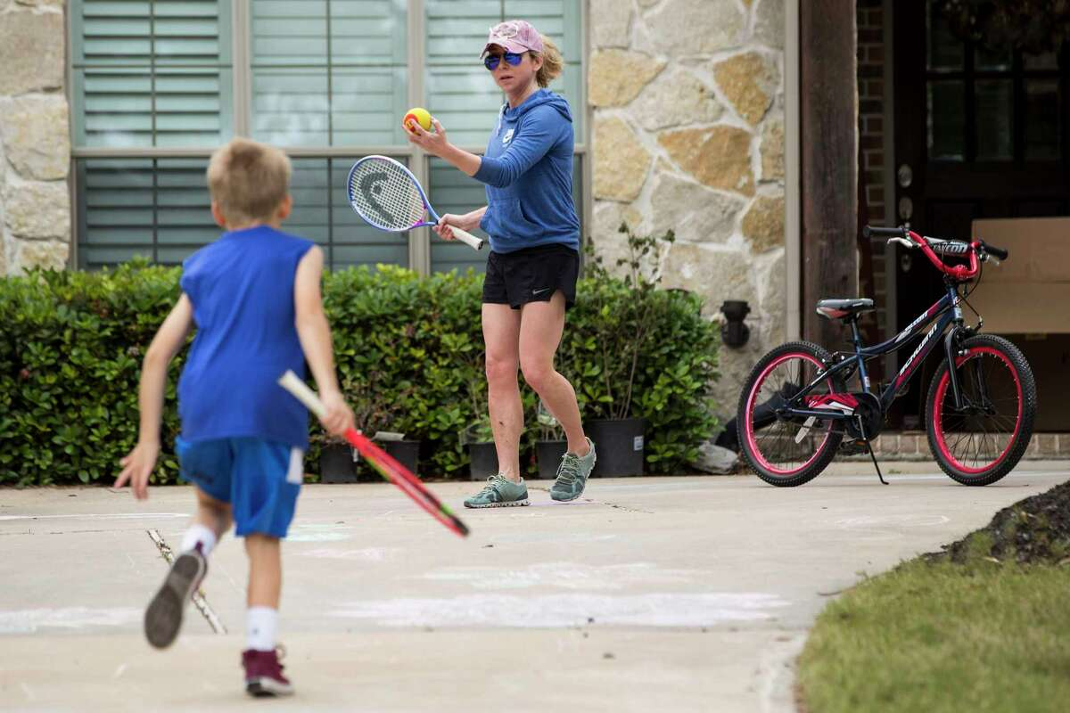 Meagan Clanahan plays outside with her son Ryan as they take a break from being indoors due to coronavirus on Friday, April 3, 2020 in Katy. During the past few years, children have dealt with major disruptive events like Harvey, Imelda and now COVID-19. Clanahan said she and her husband take time in the afternoons to play outside with their 9-year-old twins to help with their kids' anxiety.