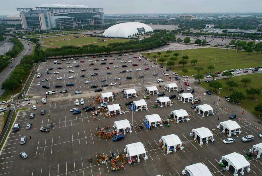 Food is distributed from tents to hundreds of cars waiting in line to receive food from a distribution site in one of the parking lots adjacent to NRG Stadium, Saturday, April 18, 2020, in Houston. The Houston Independent School District partnered with the Houston Food Bank to distribute what they said initially would be 3,000 bags of food. Photo: Mark Mulligan, Staff Photographer / © 2020 Mark Mulligan / Houston Chronicle