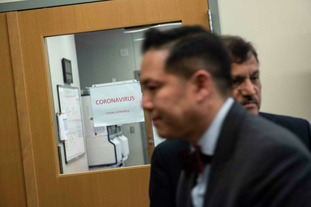 Anthony Tran, center, the public health laboratory director for the D.C. Department of Forensic Sciences, walks in front of a lab dedicated to coronavirus testing in Washington on March 30.