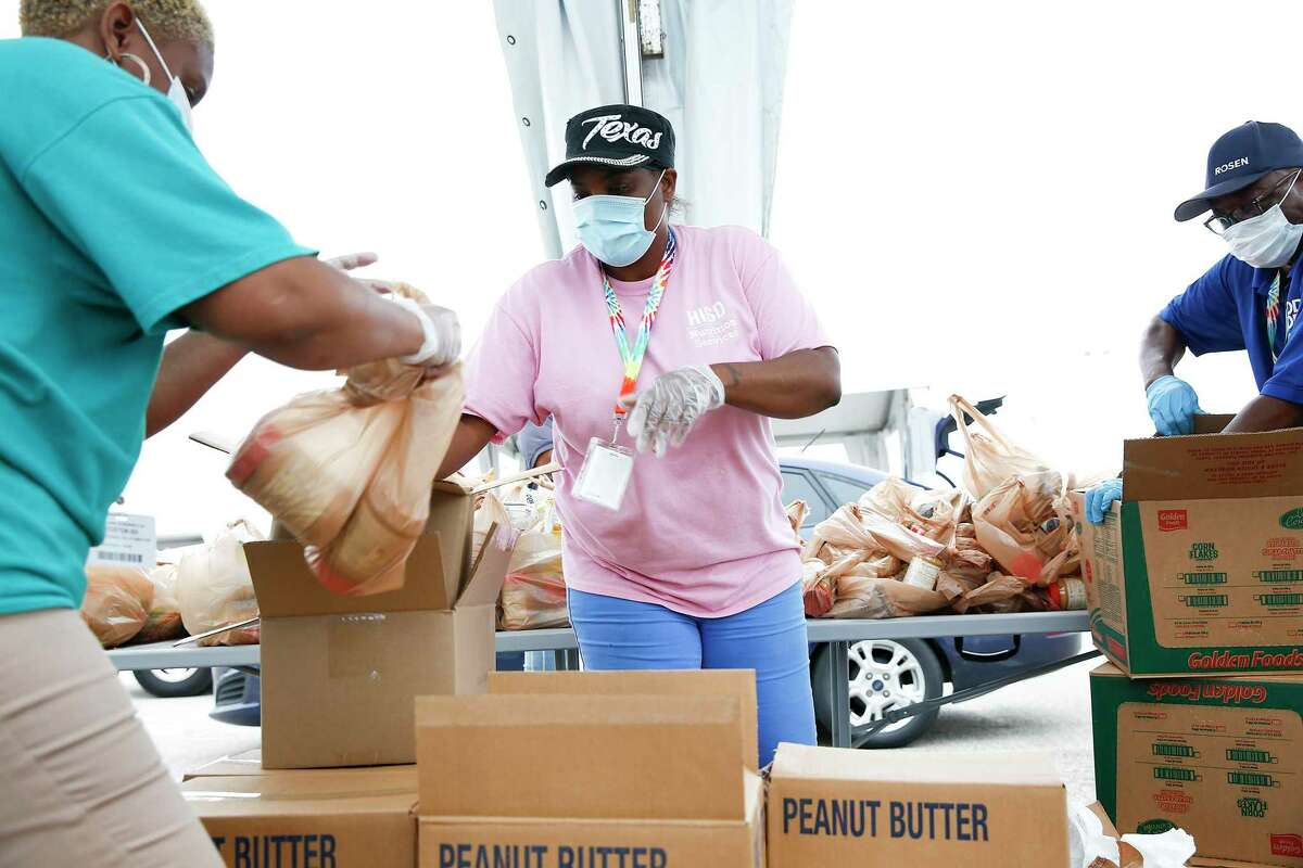 Volunteers LaToya Joseph, from left, Kanika Davis and Walter Tshitya distribute food during the Houston Food Bank and the Houston Independent School District distribution center in the parking lot of NRG Stadium in Houston on Saturday, April 18, 2020.