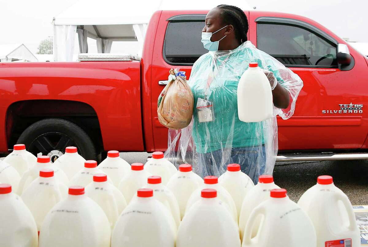 Houston Food Bank volunteer Rachel Hunt distributes milk at a mass distribution site sponsored by the food bank and the Houston Independent School District in the parking lot of NRG Stadium in Houston on Saturday, April 18, 2020.