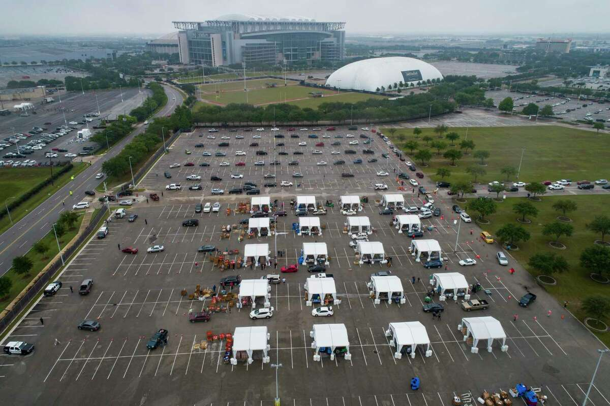 Food is distributed from tents to hundreds of cars waiting in line to receive food from a distribution site in one of the parking lots adjacent to NRG Stadium, Saturday, April 18, 2020, in Houston.