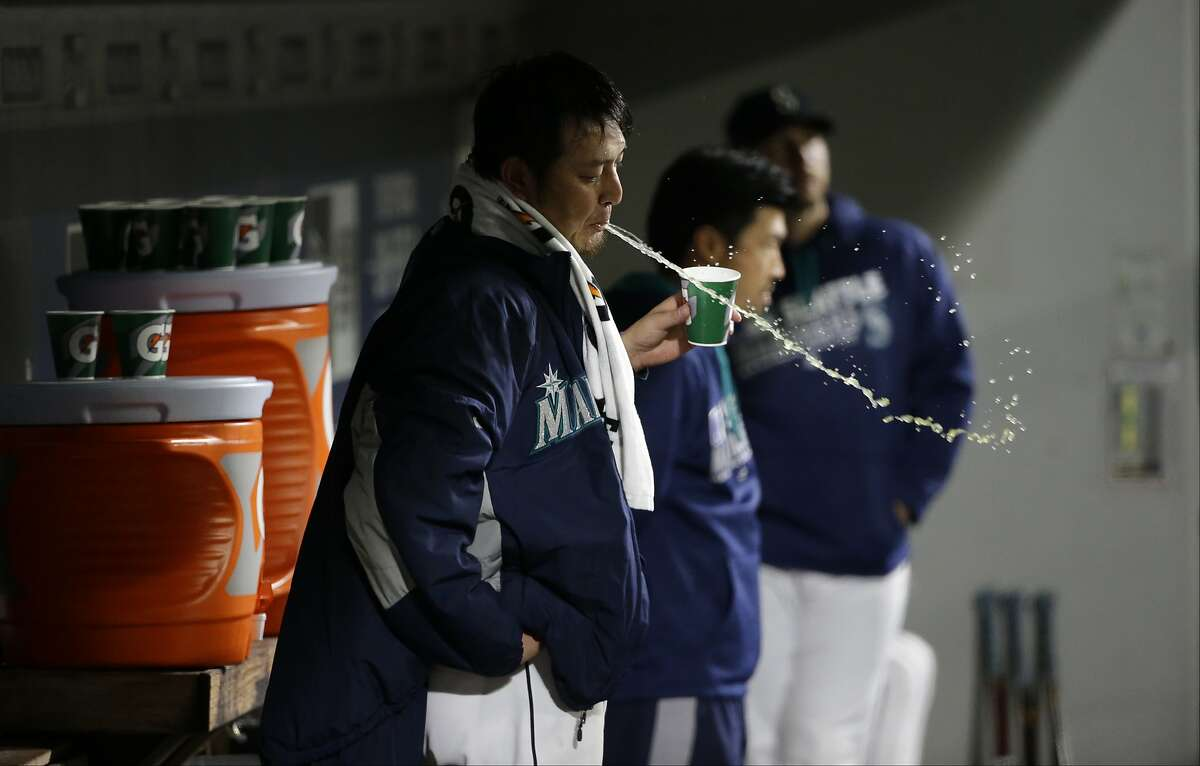 Seattle Mariners starting pitcher Hisashi Iwakuma spits his drink as he stands in the dugout after being pulled from a baseball game against the Oakland Athletics in the fourth inning, Saturday, Oct. 1, 2016, in Seattle. (AP Photo/Ted S. Warren)