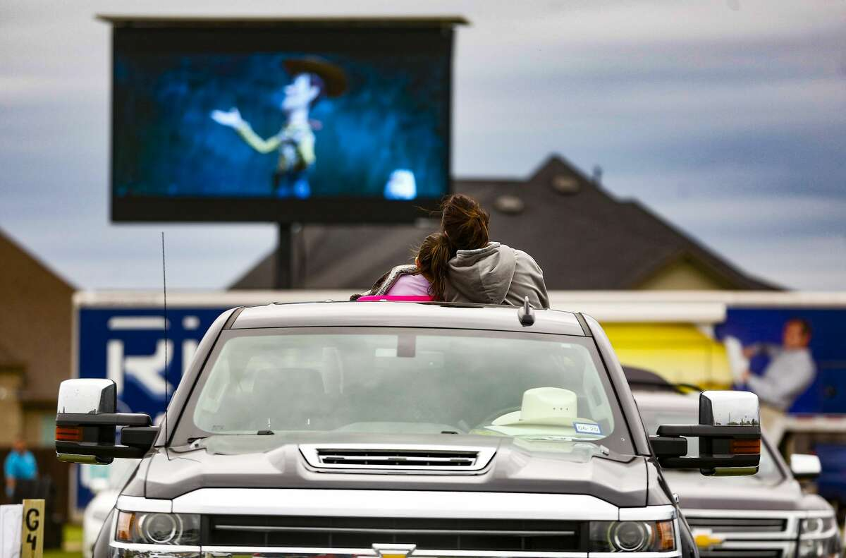 On Saturday, March 28, 2020 a community in Katy, Texas tried to create a socially-distance pop-up drive-in theater. Truck, hat, family - Texas in one image.