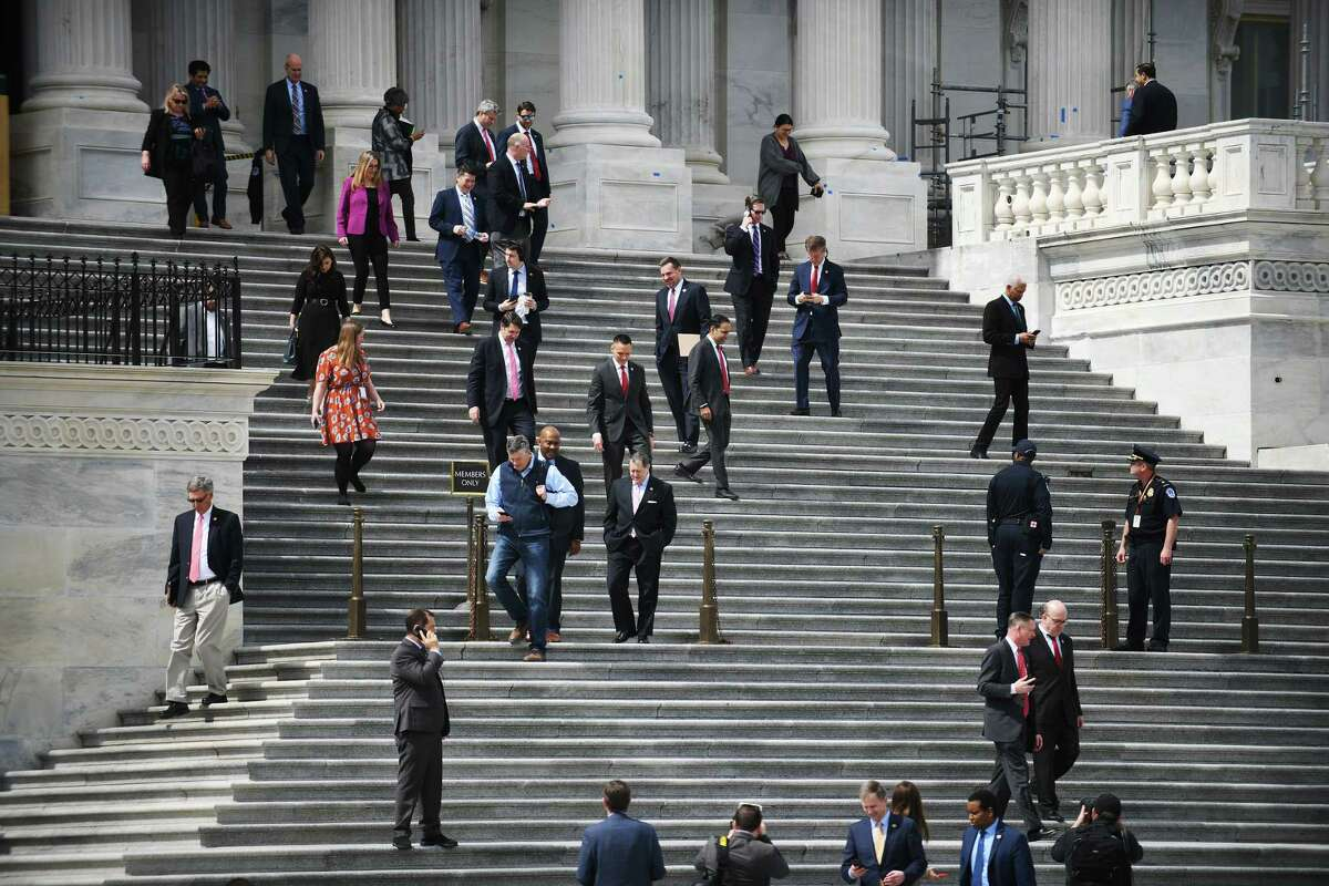 House lawmakers leave the Capitol building after voting on the emergency relief package in Washington on March 27.