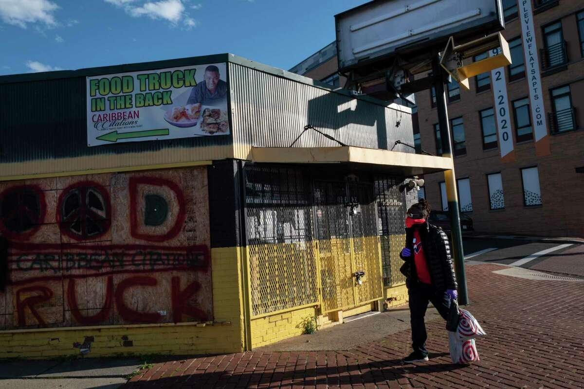 A woman, wearing a mask and gloves, walks past a shuttered business in Washington, D.C., on March 30.