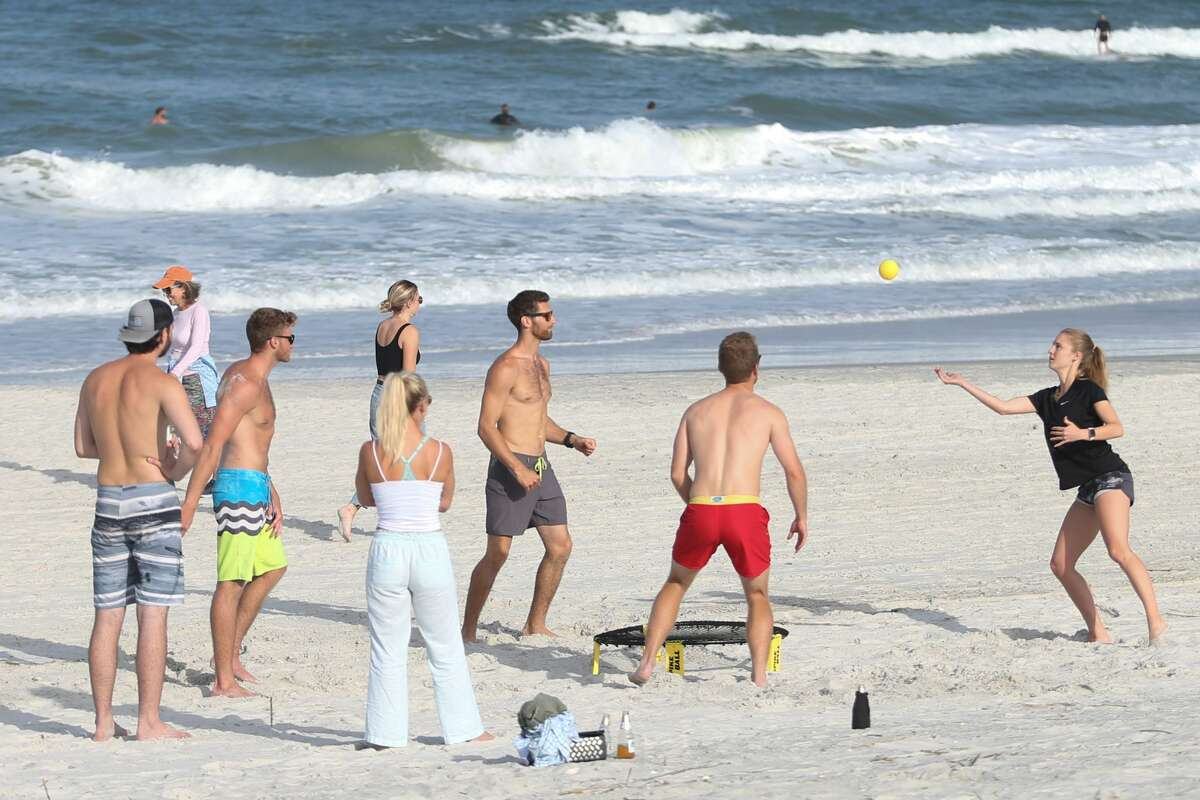 People play a game of Spike Ball on the beach in Jacksonville Beach, Fla. The sight of so many people flocking to Jacksonville beaches over the April 24-26 weekend prompted the hashtag #FloridaMorons to trend on Twitter. Several states began relaxing shelter-in-place restrictions this week.