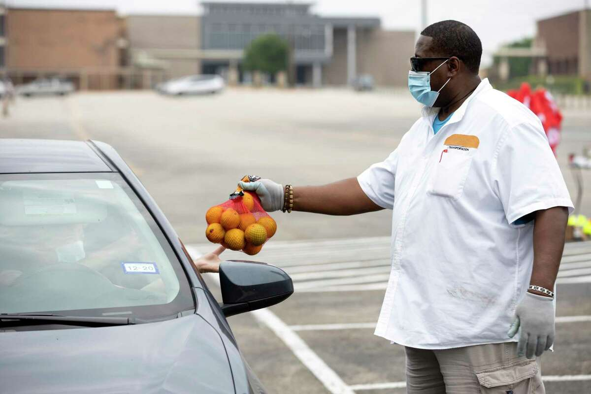 Kenneth Miller, driver for the Montgomery County Food Bank, hands a bag of oranges to a driver outside of Conroe High School, Thursday, April 9, 2020. The food bank has noticed a higher demand for food that's been steadily increasing since the COVID-19 pandemic began.