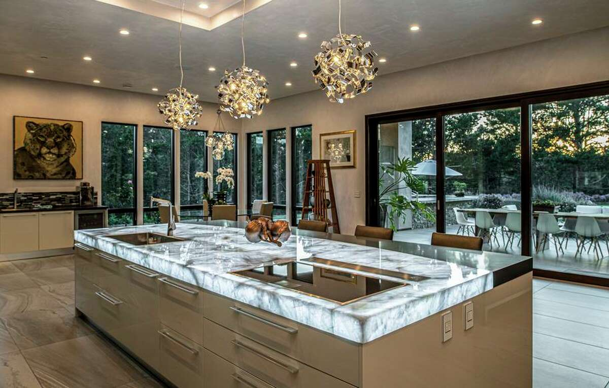 Modern pendant lights illuminate the kitchen's stone-topped island that features an induction cooktop.
