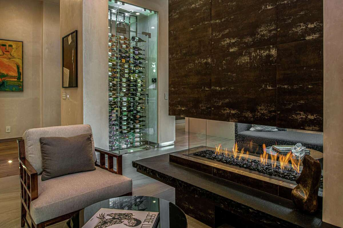 The Carmel estate home includes a temperature-controlled wine room beside a floating gas fireplace.