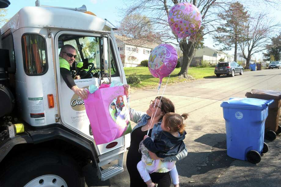 Truck drive Vinnie Yulo for Oak Ridge Waste and Recycling hands a bag of presents and balloons to birthday girl Isabella Stevens and her mother Ashley in front of their family home in Shelton on Friday. Oak Ridge Waste and Recycling delivered presents and balloons to Isabella as a surprise on her 2nd birthday Friday. Photo: Ned Gerard / Hearst Connecticut Media / Connecticut Post