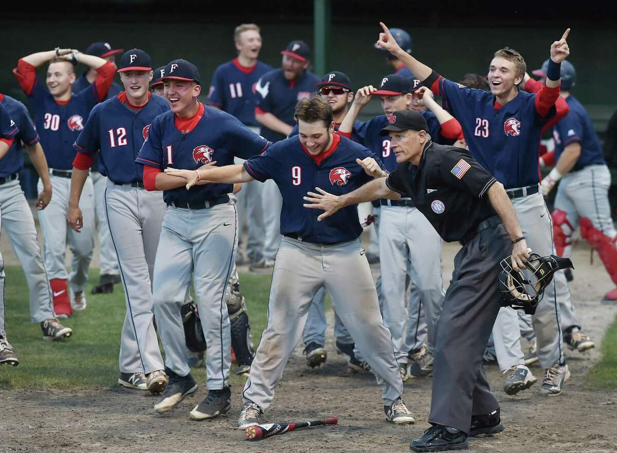 Foran captain Anthony Turlis (9) is held back by the home plate umpire during their win over North Haven in the 2017 CIAC class L baseball championship game in Middletown.