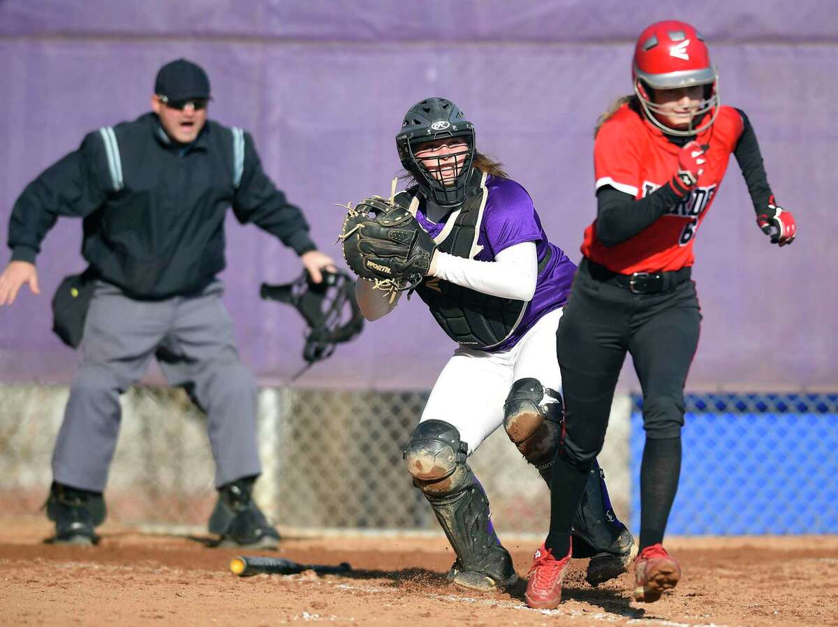 Westhill catcher Maddy Cortell (17) fields a foul ball in front of the umpire as Fairfield Warde's Molly Meehan heads to first base during a 2018 FCIAC softball game.
