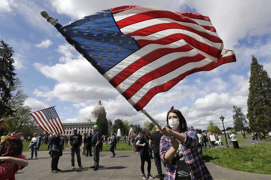 """Janell Sorensen, of Woodland, Wash., waves a flag as demonstrators begin to gather at the Capitol for a protest opposing Washington state's stay-home order to slow the coronavirus outbreak Sunday, April 19, 2020, in Olympia, Wash. Washington Gov. Jay Inslee has blasted President Donald Trump's calls to """"liberate"""" parts of the country from stay-at-home and other orders that are designed to combat the spread of the coronavirus. Inslee says that Trump is fomenting a potentially deadly """"insubordination"""" among his followers before the pandemic is contained. (AP Photo/Elaine Thompson) Photo: Elaine Thompson, Associated Press"""