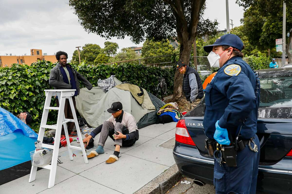 A police officer asks a group of homeless men to social distance themselves from one another outside a tent encampment on Oak Street on Sunday, April 19, 2020 in San Francisco, California.