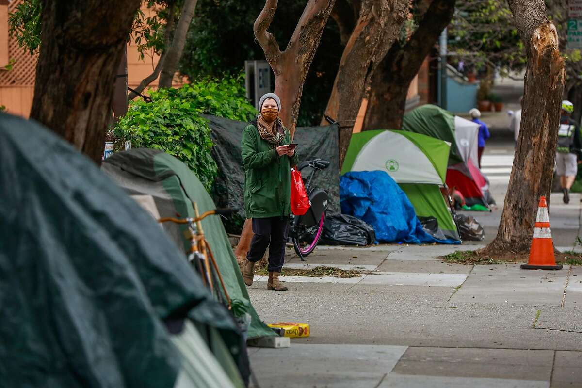 A pedestrian passes by a tent encampment on Broderick Street on Sunday, April 19, 2020 in San Francisco, California.