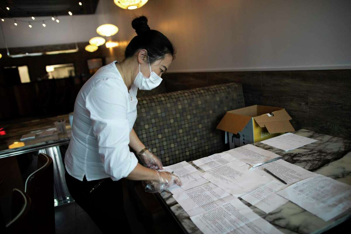 Yunan Yang, founder of the Pepper Twins restaurant, examines a list Sunday in Houston of first responders and medical professionals verified to receive protective masks.
