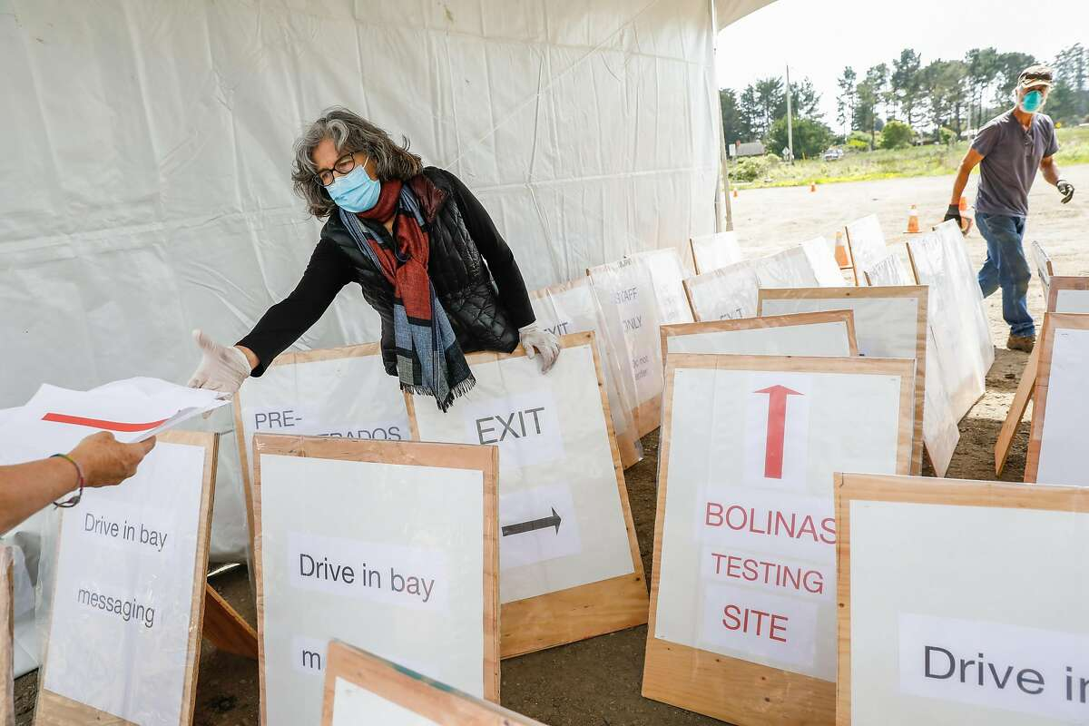 Aenor Sawyer (left) helps to unload signage while setting up a testing site for people to get their blood tested for covid-19 in Bolinas, California on Sunday, April 19, 2020.