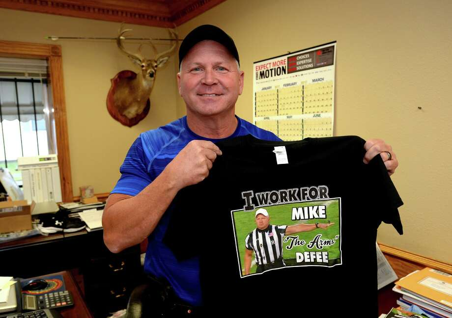An overnight internet sensation, Mike Defee holds one of several shirts worn by his coworkers Tuesday after memes depicting him as a muscular referee at the National Championship game went viral. Photo taken Tuesday, January 10, 206 Guiseppe Barranco/The Enterprise Photo: Guiseppe Barranco, Photo Editor / Guiseppe Barranco/The Enterprise
