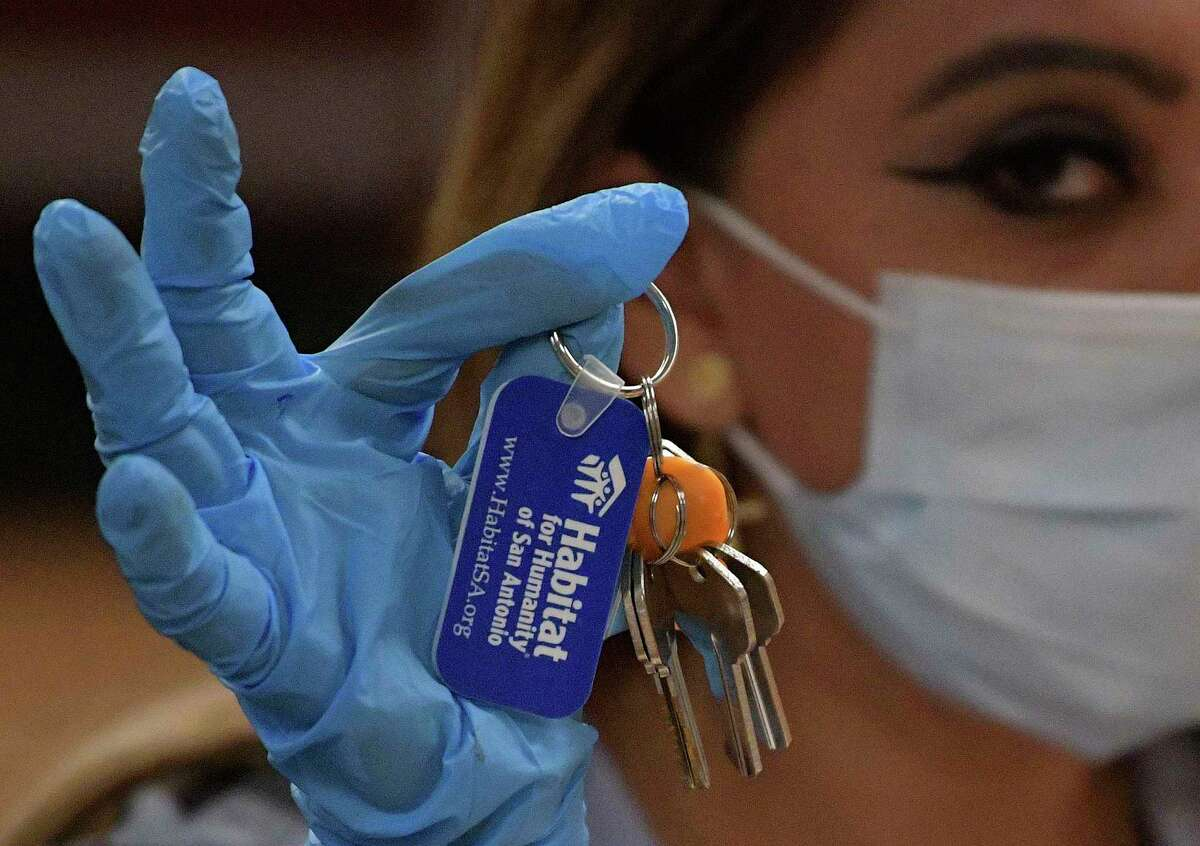Aida Nambo, 24, displays the keys to her family's new Habitat for Humanity home on Wednesday, April 15, 2020. The organization's house dedication ceremonies are now being done on video due to the coronavirus pandemic, and people doing business with the organization must wear face masks.