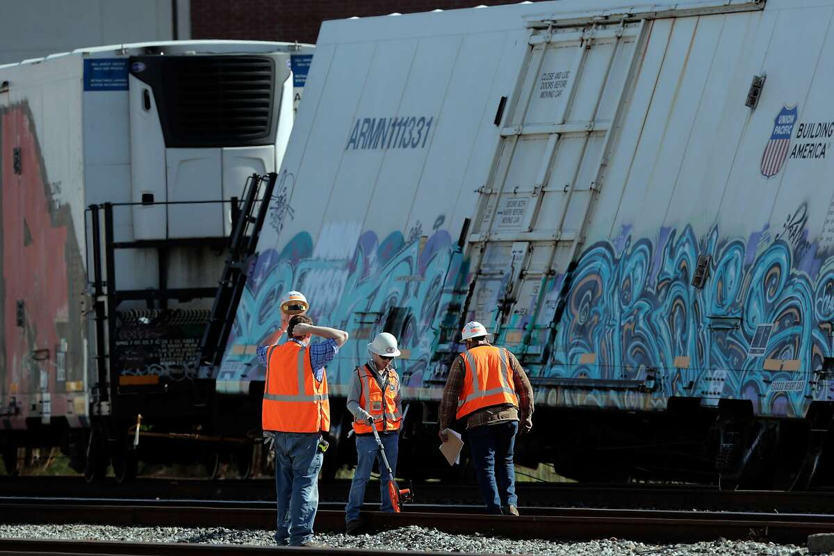 Union Pacific workers take measurements of the damage on the tracks where a Union Pacific freight train derailed near the Hyatt Place Hotel at Shellmound Street under the Powell Street overpass in Emeryville, Calif., on Sunday, April 19, 2020. The rail company said 6 cars derailed and blocked several street crossings for several hours before the train was separated and the remainder of the train that was still on the tracks was removed.