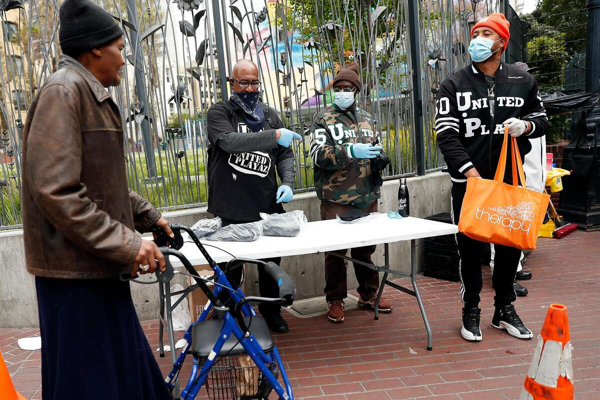 (left to right) United Playaz' Wallace Ferguson, Boogie Butler and Jamal Trulove hand out masks and hand sanitizer at the corner of Eddy and Jones Streets in San Francisco, Calif., on Sunday, April 19, 2020.