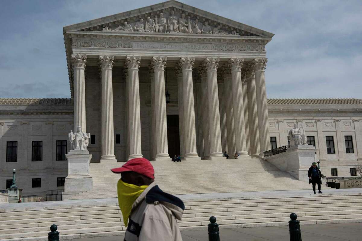 A man wearing a makeshift mask walks in front of the U.S. Supreme Court on March 24, 2020.