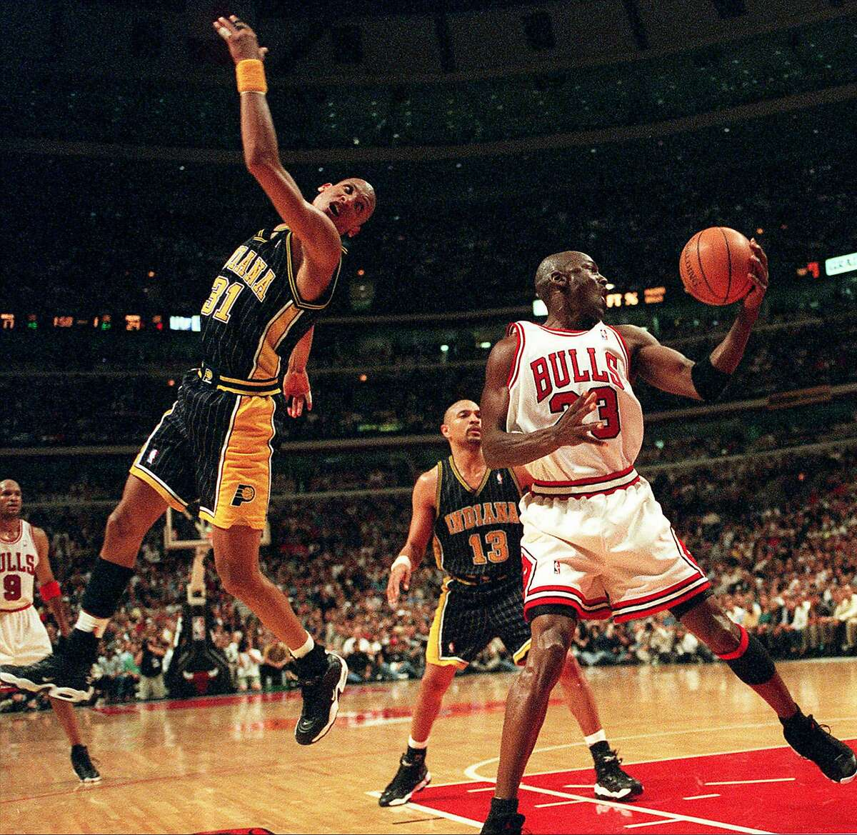 Chicago Bulls' Michael Jordan keeps the ball from Indiana Pacers' Reggie Miller during the first quarter of a playoff game on May 19, 1998 at the United Center in Chicago, Ill. (Charles Cherney/Chicago Tribune/TNS)