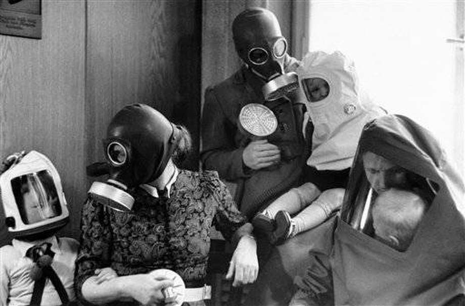 Gas masks of various types to suit adults, children and babies have now been issued to families in Germany. Those for children closely resembled the bag type of masks, with air supplied by bellows, which were tried out for babies and young children in this country. A German family wearing the different types of gas masks issued to them, in Berlin, on April 20, 1939. (AP Photo)