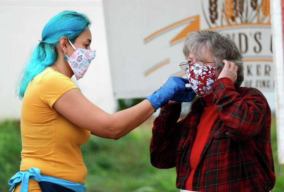 Blooming Tree Soaps owner Irene Fernandfez, left, helps Jeanne McCowan adjust her facemask at the Farmer's Market on Tamina, Saturday, April 18, 2020, in Magnolia. Photo: Jason Fochtman, Houston Chronicle / Staff Photographer / 2020 © Houston Chronicle