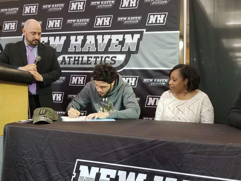 Former Hillhouse boys basketball standout Joey Kasperzyk, center, signs a National Letter of Intent to play basketball at Division I Bryant University. He is flanked by his mother, Lanisha Harris, right, and Eric Patchkofsky, New Haven's citywide athletic director. April 25, 2018 Photo: Joe Morelli / Hearst Connecticut Media / Joe Morelli / Hearst Connecticut Media / Greenwich Time Contributed