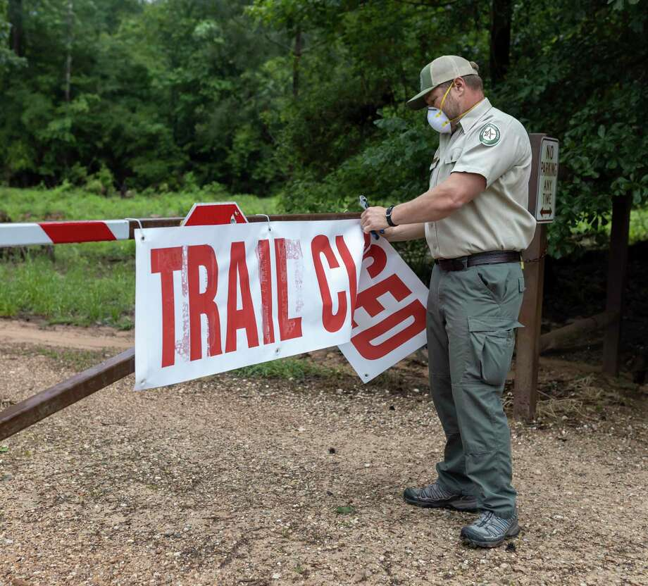 Resource Specialist, Jeff LeBlanc, cuts zip ties off of a sign stating 'trail closed,' Monday, April 20, 2020. During Gov. Greg Abbott's 3 phase plan to reopen the state, he also put restrictions in place to ensure social distancing is practiced on the trails. Photo: Gustavo Huerta, Houston Chronicle / Staff Photographer / Houston Chronicle © 2020