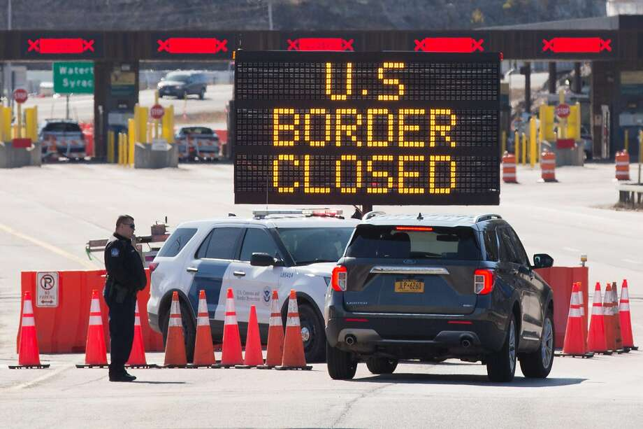 (FILES) In this file photo US Customs officers speaks with people in a car beside a sign saying that the US border is closed at the US/Canada border in Lansdowne, Ontario, on March 22, 2020. - Canada's GDP plunged 9 percent in March due to travel restrictions and temporary business closures to fight the coronavirus pandemic, dragging down first quarter growth to -2.6 percent, Statistics Canada said on April 15, 2020. The estimates marked the biggest one-month GDP drop on record (since 1961), but beat analyst forecasts as low as -11.7 percent for the quarter. (Photo by Lars Hagberg / AFP) (Photo by LARS HAGBERG/AFP via Getty Images) Photo: Lars Hagberg / AFP Via Getty Images
