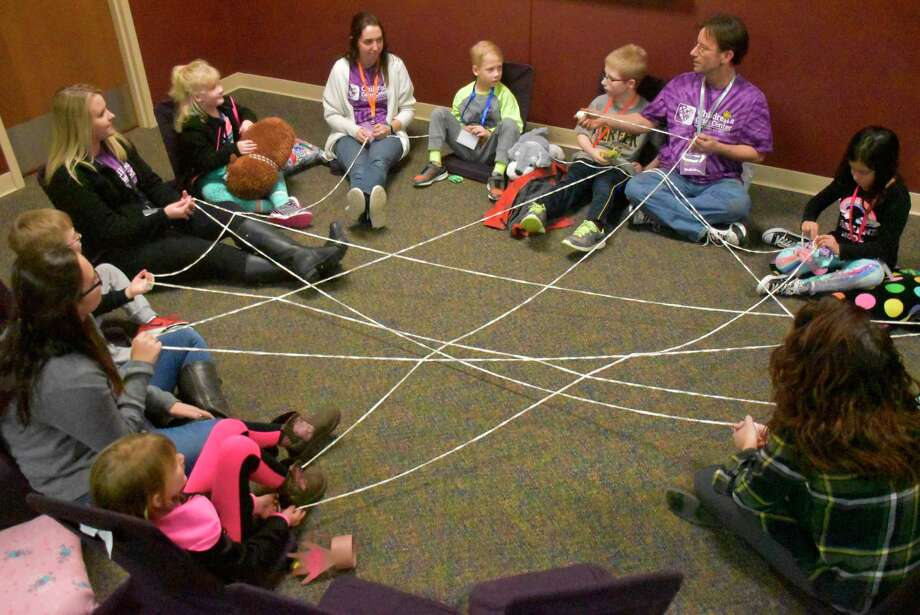 """Children participate in an activity at Children's Grief Center of the Great Lakes Bay Region demonstrating the """"invisible string"""" which connects us all. (Photo provided)"""