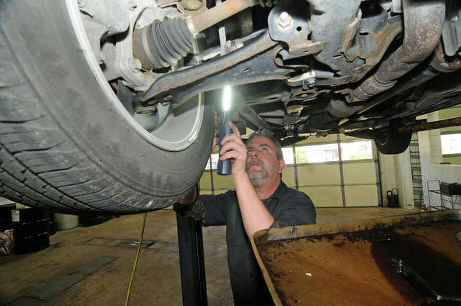 Brad Pedersen of Prairie Street Auto in Bethalto works on a customer's car. His business is down 25 percent since the pandemic began.