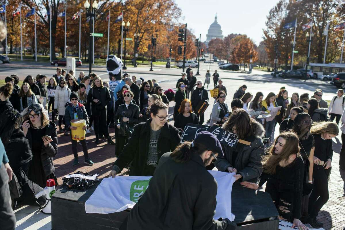 The D.C. Chapter of Fridays for Future pauses its procession to hold a die-in during the Black Friday Funeral for Future demonstration at Union Station in Washington. (