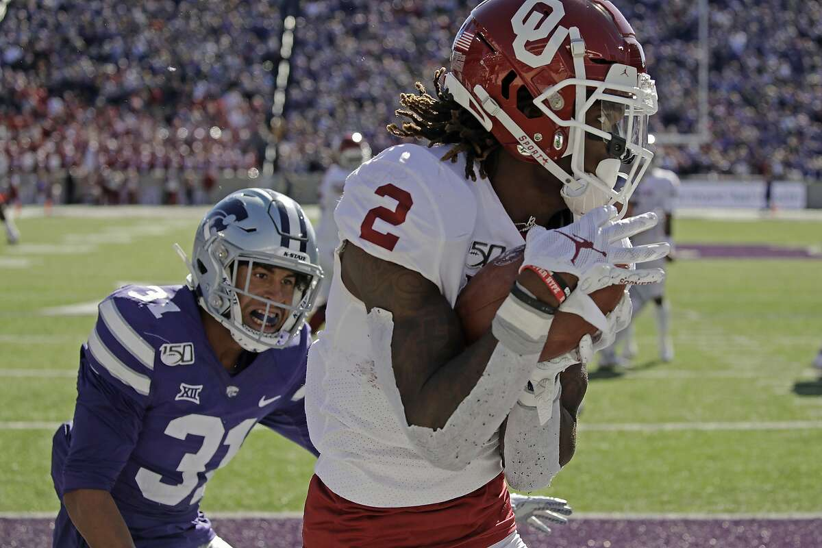 FILE - In this Oct. 26, 2019, file photo, Oklahoma wide receiver CeeDee Lamb (2) catches a pass in the end zone under pressure from Kansas State defensive back Jahron McPherson (31) to score a touchdown during the second half of an NCAA college football game in Manhattan, Kan. This year's NFL draft features a superb group of wide receivers, including Lamb, who are expected to make immediate impacts in the NFL.(AP Photo/Charlie Riedel, File)