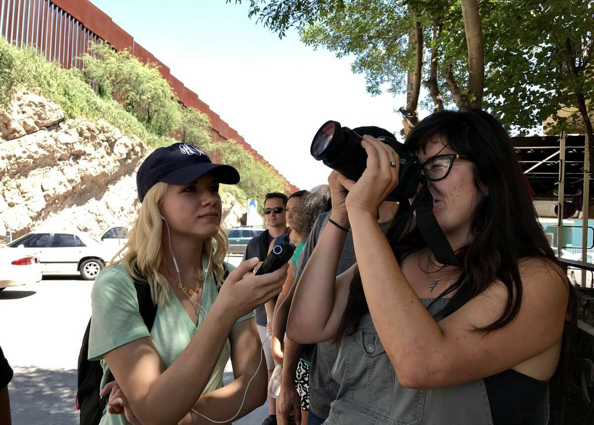 University of Arizona journalism students test their equipment in Nogales, Sonora, Mexico, with the southern border wall looming in the background. The students are in a class that reports along the border; stories from the class are often published in professional media outlets.