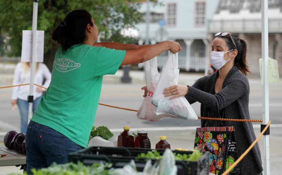 Josie Scherman purchases produce from Peas Farm at the Tomball Farmers Market last Saturday. Photo: Jason Fochtman, Houston Chronicle / Staff Photographer / 2020 © Houston Chronicle