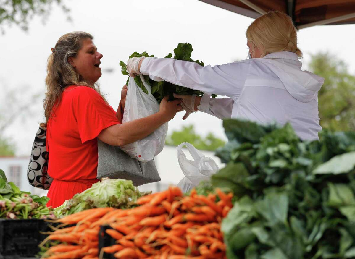 Jennifer Kurzy accepts bags of produce at the Tomball Farmers Market, Saturday, April 18, 2020, in Tomball.