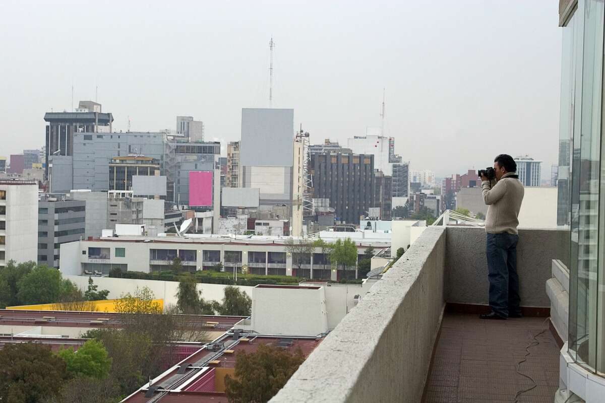 A Mexican photojournalist captures photos of the city from a balcony.